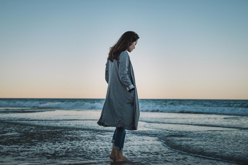 Femme en veste d'hiver face à la plage