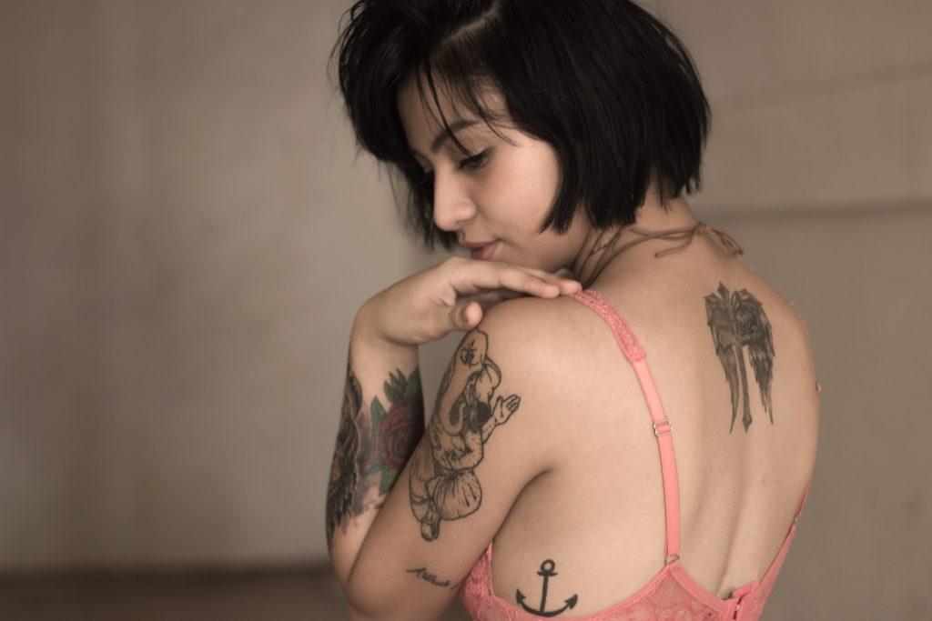 Une femme avec des tatouages qui porte un soutizn-gorge rose