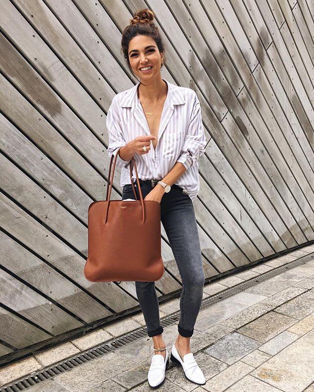 Jeune femme qui porte une blouse blanche, un jean noir et une paire de mocassins blancs