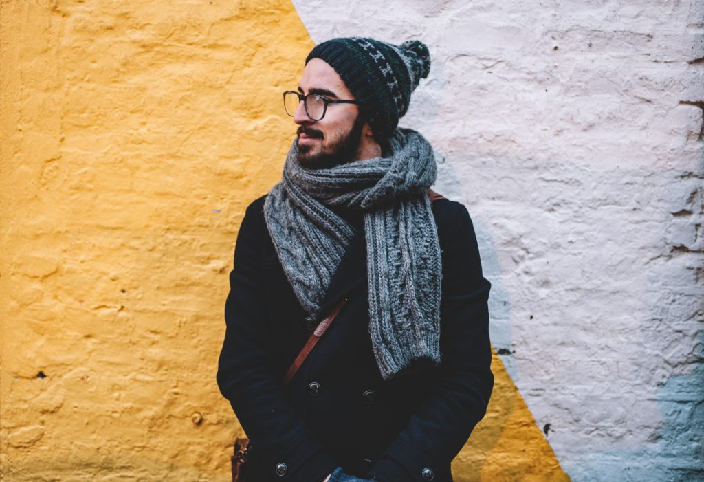 homme portant un bonnet un manteau foncé et une écharpe grise devant un mur blanc et jaune