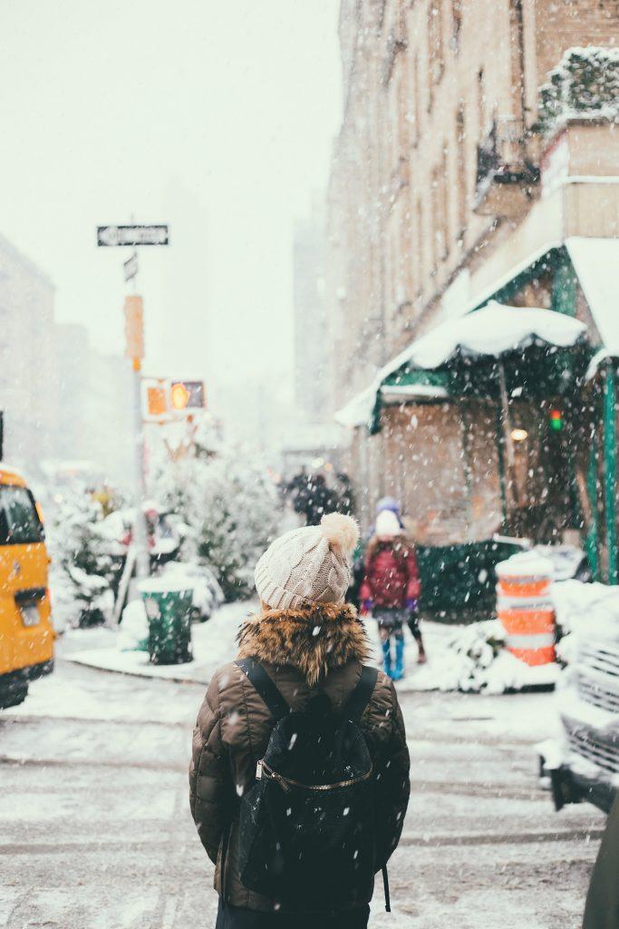 femme se tenant dans la rue en hiver sous la neige portant un bonnet un manteau kaki avec de la fourrure au niveau de la capuche avc un sac à dos foncé
