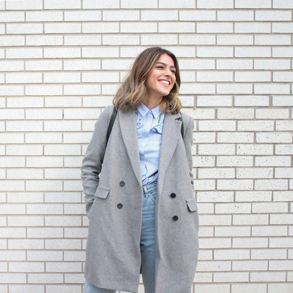 femme portant une chemise bleues un jean et un manteau long gris devant un mur en brique blanc