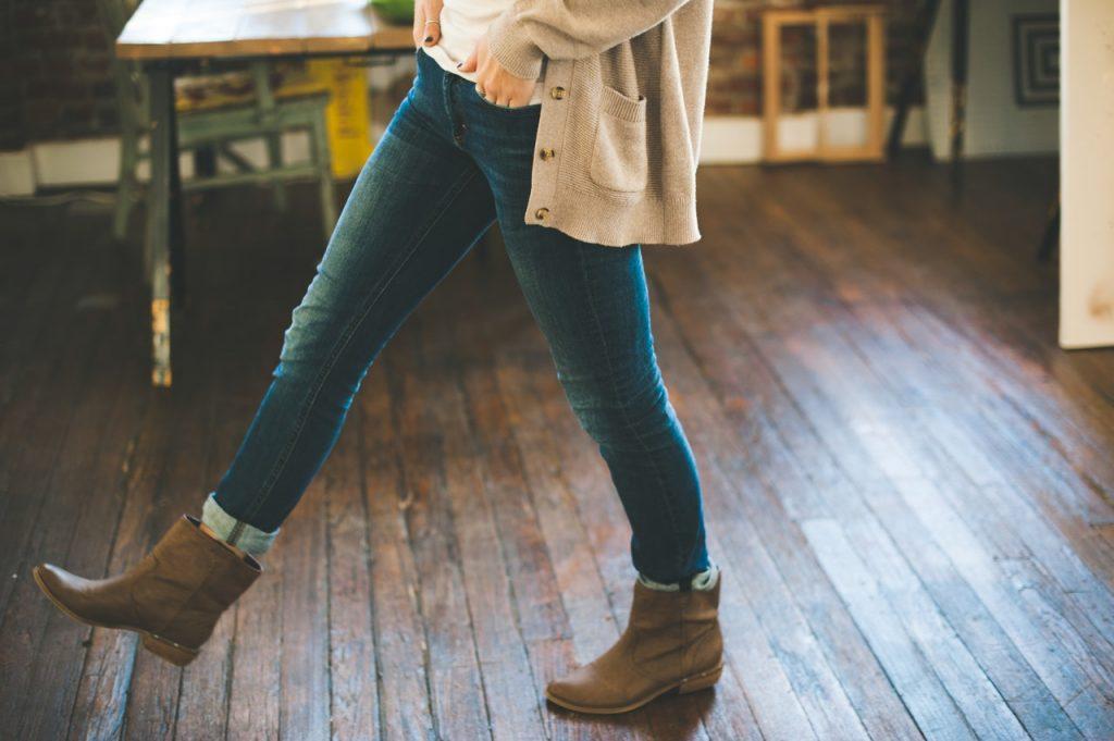 femme portant un jean un gilet long beige un haut blanc et des bottines marron