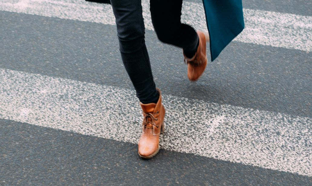 femme portant un manteau long un pull clair un jean foncé et des bottines marron